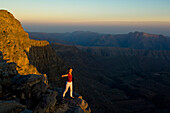 Woman with outstretched arms, feeling the upwind, sunset, Sayh plateau, Mountain landscape, Hajjar mountains, Kashab, Khasab, Musandam, Oman
