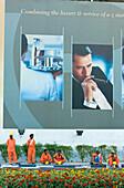 Construction workers having a break beneath an advertisement for luxury, Dubai, United Arab Emirates