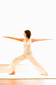 Mid adult woman practising yoga (Warrior Pose), yoga studio at Linz, Austria