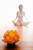 Mid adult woman practising yoga (Lotus pose), Lotus blosom in foreground, yoga studio at Linz, Austria