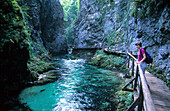Woman walking through Vintar Gorge in Triglav National Park, Slovenia