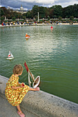 Girl playing with toy sailing boat in a pond, Jardin du Luxembourg, largest public park in Paris, 6e Arrondissement, Paris, France