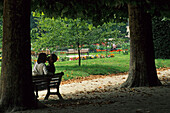 Kissing couple sitting on a park bench, summer, Paris, France