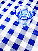 Beverage, Beverages, Blue, Blue tone, Checkered, Chequered, Clean, Color, Colour, Drink, Drinks, Empty, Glass, Glasses, Monochromatic, Monochrome, Object, Objects, One, One item, Still life, Table, Tablecloth, Tablecloths, Tables, Thing, Things, Toned, L5