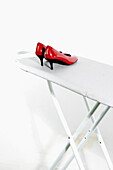 Color, Colour, Concept, Concepts, Fashion, Feminine, Footgear, Footwear, Heels, Housework, Indoor, Indoors, Inside, Interior, Ironing board, Ironing boards, Ironing-board, Object, Objects, Odd, Pair, Pairs, Red, Shoe, Shoes, Still life, Strange, Style, Th