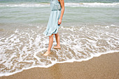 Adult, Adults, Anonymous, Barefeet, Barefoot, Beach, Beaches, Calm, Calmness, Chill out, Chilling out, Coast, Coastal, Color, Colour, Contemporary, Daytime, Dress, Dresses, Ephemeral, Exterior, Female, Foam, Foamy, Froth, Human, Leisure, One, One person,