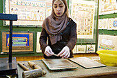 Woman showing the process to make papyrus for paintings. Cairo. Egypt.