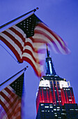 American flags and Empire State Building. New York City, USA