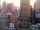 New York, NY: A flag waves in the early morning light of midtown Manhattan.
