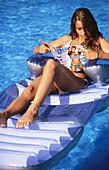 Woman reading in swimming-pool.