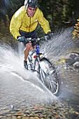 Man splashing through water on a mt. biking in Sun Valley, Idaho. USA