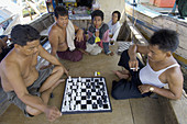 indonesian fishermans playing chess on a boat used as shop. muara angke fish market. jakarta north. indonesia. asia.