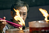 an indonesian man light up incense sticks in Vihara Dharma Bhakti temple in chinatown. west jakarta. indonesia. asia.