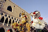 Two people at San Marco dressed in lavish colourful costumes for a masquerade at Carnival. Venice, Italy