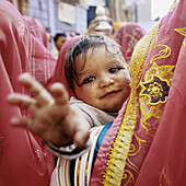 Young child is being held by women in colourful sari at a traditional Rajasthan wedding. Child has black make up around eyes This is done from birth to ward off evil eyes This wedding was held in Jodhpur. India.