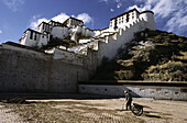 Older male with wheelbarrow fixing the tiled pavement outside of Potala Palace in Lhasa, Tibet. China.