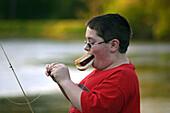11 year old boy, eating hotdog while baiting hook for fishing