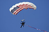 Man parachuting down to the ground with an American flag as a canopy, against a clear blue sky