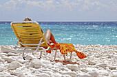 Woman on beach on a chair. Cobble beach. Curaçao. Netherlands Antilles.