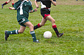 Teen girls, in their uniforms, competing in a soccer game.