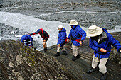 Ecotourists descending from Franz Joseph glacier with help from guide, Westland National Park, New Zealand.