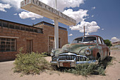 Abandoned, Antique, Arizona, Auto, Automobile, Broken headlights, Brown, Brush, Buick, Chrome, Clouds, Color, Colour, Decrepit, Desert, Deserted, Gas station, Green, Grill, Old, Paint, Porthole, Portholes, Roadmaster, Rundown, Rust, Stone building, N17-56