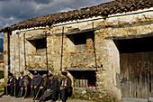 Retired men sunbathing in Cuacos de Yuste. Cáceres province, Extremadura, Spain