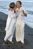 Middle-aged couple on the beach, holding champagne glasses