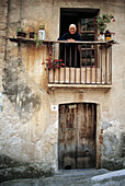 Woman in black looking out from balcony in Sperlinga. Sicily, Italy
