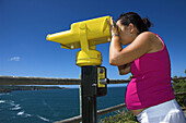 Young pregnant woman with seaside telescope, looking to the future.