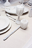 Dinner service wrapped in white linen.