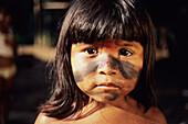 Sateré-Maué girl in the Amazon region gazes curiously into the camera.