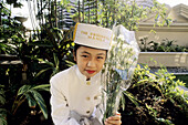Girl in uniform holding flowers in Manila, Philippines