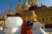 Novice monk holding an alms bowl in fron of the Shwezigon Pagoda, Bagan, Myanmar (Burma)