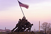Statue of Marines holding American flag, Iwo Jima Memorial (United States Marine Corps War Memorial), with U. S. Capitol Building and Washington Monument in background, Arlington, Virginia