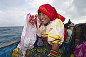 Kuna Indian women in native costume with Mola embrodery blouses leaving Corbisky Island in a dugout canoe, San Blas Islands (Kuna Yala), Caribbean Sea, Panama
