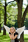 Mid adult woman wearing angel wings in a park
