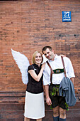 Angel, young woman with wings standing next to a man in traditional dress, Munich, Bavaria, Germany