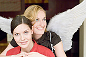 Mid adult woman wearing angel wings embracing woman from behind