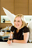 Angel, young woman with wings drinking a glass of red wine, restaurant, Munich, Bavaria, Germany