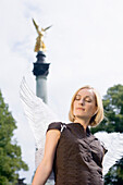 Mid adult woman wearing angel wings near Friedensengel, Munich, Bavaria, Germany