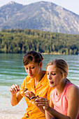 Two young women sitting at lake Walchensee while eating, Bavaria, Germany