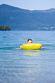 One young woman, girl, lying on an air mattress on the lake, Lake Walchensee, Upper Bavaria, Bavaria, Germany