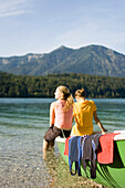 Two young women sitting on a boat at lake Walchensee, Bavaria, Germany