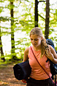 Young woman with backpack and sleeping pad hiking through forest