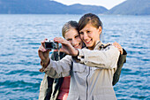 Two young women, girls, taking a photograph of themselves, Lake Walchensee, Upper Bavaria, Bavaria, Germany