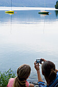 Two young women taking a photo of lake Walchensee, Bavaria, Germany