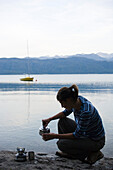 A young woman making a drink on a cooking stove at Lake Walchensee, Upper Bavaria, Bavaria, Germany