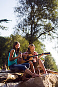 Two young women sitting on the banks of the river Isar in the evening, playing a guitar, Munich, Bavaria, Germany