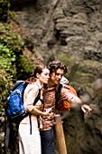 Couple hiking, man showing woman something interesting, Partnachklamm, Garmisch-Partenkirchen, Bavaria, Germany
